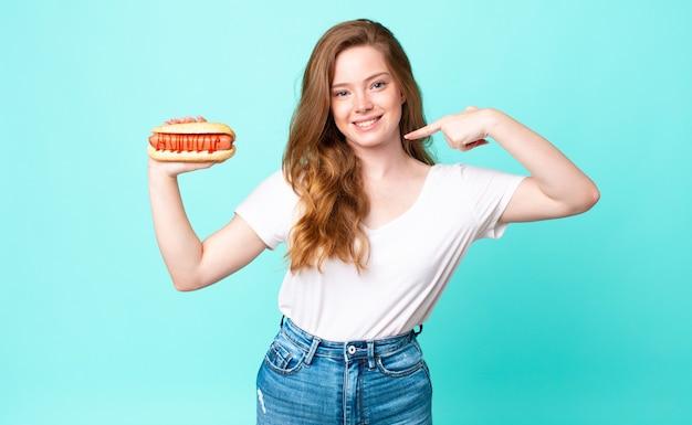 Mooie vrouw met rood hoofd die vol vertrouwen glimlacht, wijst naar haar eigen brede glimlach en een hotdog vasthoudt
