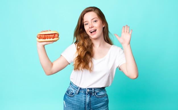 Mooie vrouw met rood hoofd die vrolijk lacht, met de hand zwaait, je verwelkomt en begroet en een hotdog vasthoudt