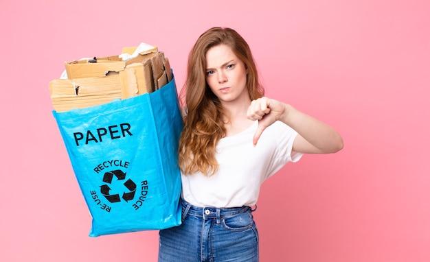 Mooie vrouw met rood hoofd die zich boos voelt, duimen naar beneden laat zien en een zak van gerecycled papier vasthoudt