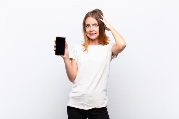 Mooie vrouw met rood hoofd, gestrest, bezorgd, angstig of bang, met de handen op het hoofd, in paniek bij een fout met een smartphone