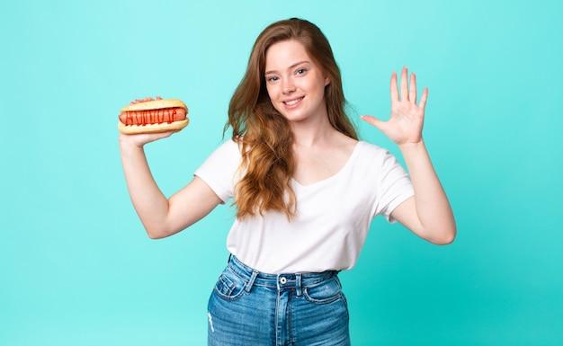 Mooie vrouw met rood hoofd lacht en ziet er vriendelijk uit, toont nummer vijf en houdt een hotdog vast