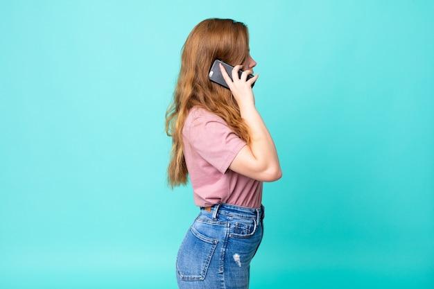 Mooie vrouw met rood hoofd op profielweergave denken, fantaseren of dagdromen en een smartphone gebruiken