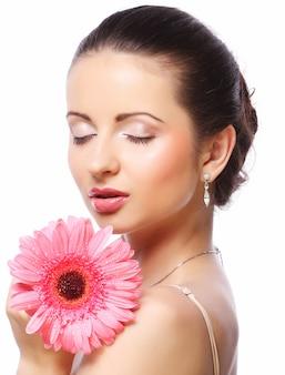 Mooie vrouw met roze bloem die op wit wordt geïsoleerd