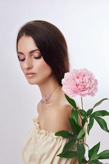 Mooie vrouw met roze bloem in haar hand