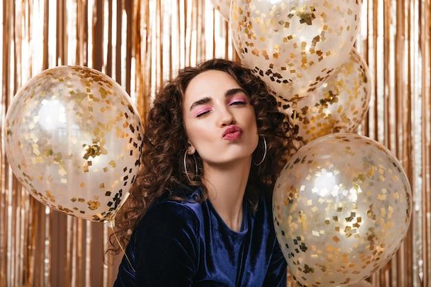 Mooie vrouw met roze oogschaduw knipoogt op gouden achtergrond met ballonnen