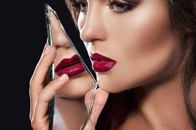 Mooie vrouw met scherven van spiegel