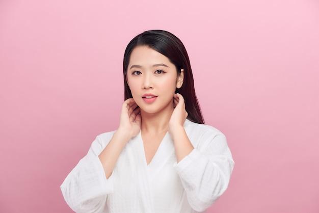 Mooie vrouw met schone huid geïsoleerd op roze