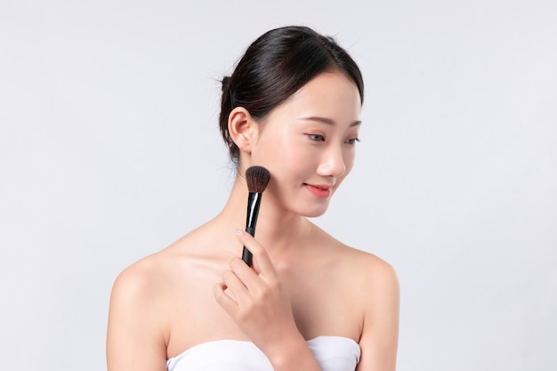Mooie vrouw met schone huid met make-up borstel