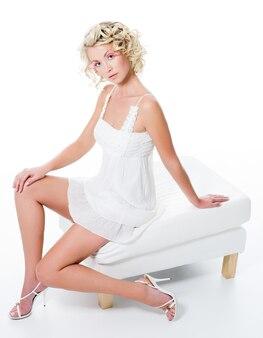 Mooie vrouw met sexy benen zit op witte stoel - hoge hoek