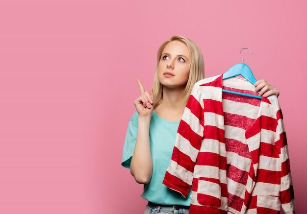 Mooie vrouw met shirt op een hanger op roze muur