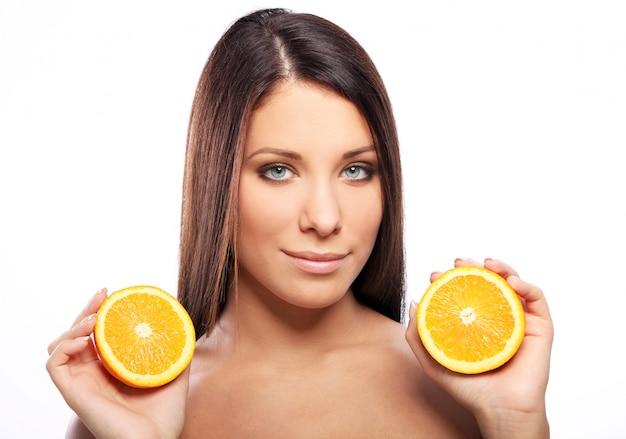 Mooie vrouw met sinaasappel in handen