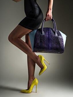 Mooie vrouw met slanke benen in gele hoge hakken. modieus meisje houdt stijlvolle blauwe tas. glamour stijlvol concept. kunst. vrouw loopt na het winkelen. onherkenbaar vrouwtje.