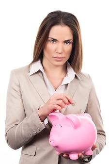 Mooie vrouw met spaarvarken en muntstuk