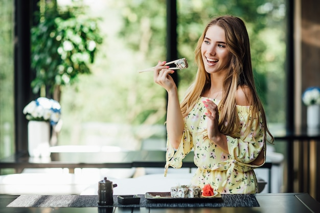 Mooie vrouw met stokjes met sushi en poseren