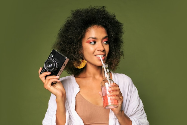 Mooie vrouw met strak kapsel poseren met camera en limonade drinken