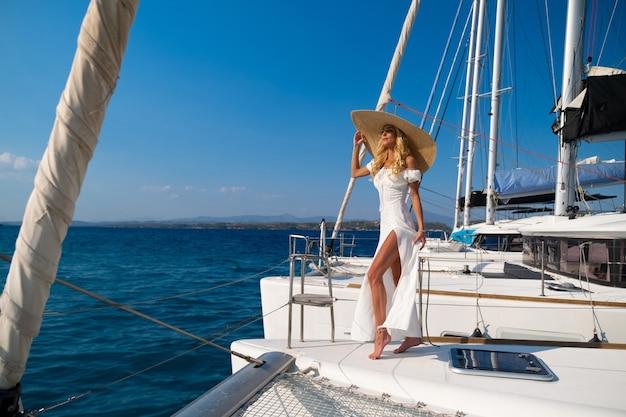 Mooie vrouw met strohoed en witte jurk op een jacht geniet van de reis spetses griekenland europa