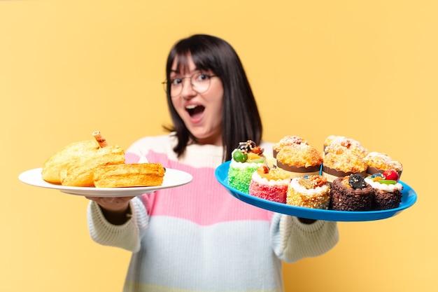 Mooie vrouw met taarten en cupcakes
