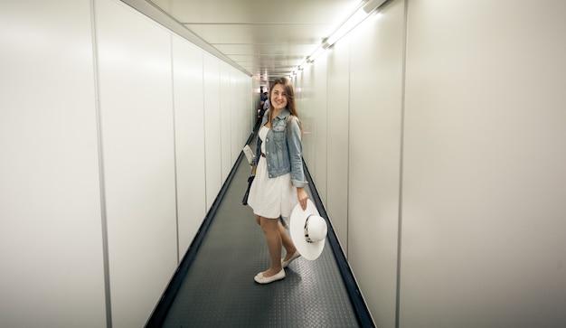 Mooie vrouw met tassen wandelen bij de instappoort op de luchthaven