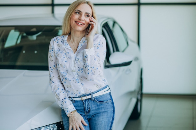 Mooie vrouw met telefoon in autoshowroom