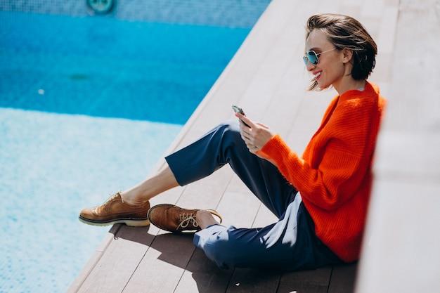 Mooie vrouw met telefoon zitten bij het zwembad