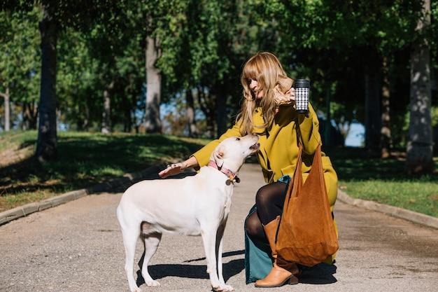 Mooie vrouw met thermosbakken die hond petting