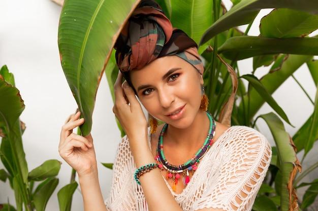 Mooie vrouw met tulband op hoofd, kleurrijke oorbellen en boho ketting poseren