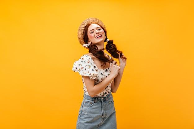 Mooie vrouw met twee paardenstaarten glimlacht koket. vrouw in hoed, zomerbovenkant en denimrok poseren op een oranje achtergrond.