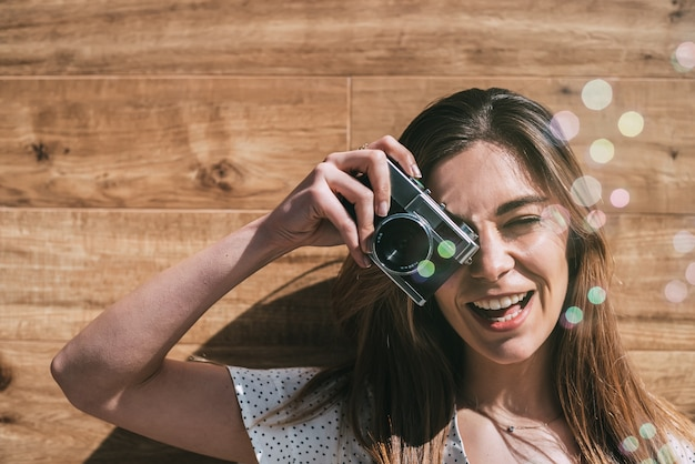 Mooie vrouw met uitstekende oude camera met zeepbels die foto nemen