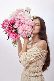 Mooie vrouw met veel roze bloemen in haar handen.