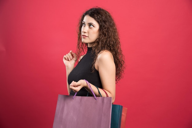 Mooie vrouw met veel tassen op rood