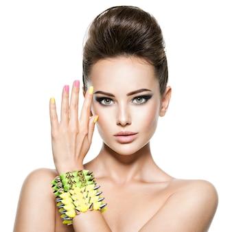 Mooie vrouw met veelkleurige nagels en bezaaid armband bij de hand