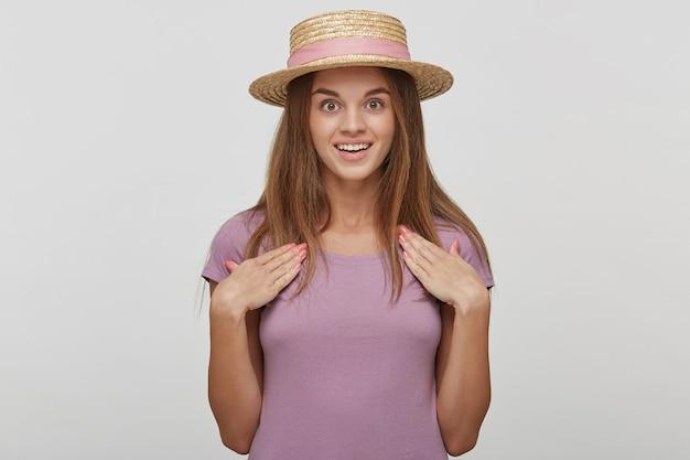 Mooie vrouw met verbaasde uitdrukking, kijkt met afgeluisterde ogen en houdt de mond open, wijst met beide handpalmen naar zichzelf