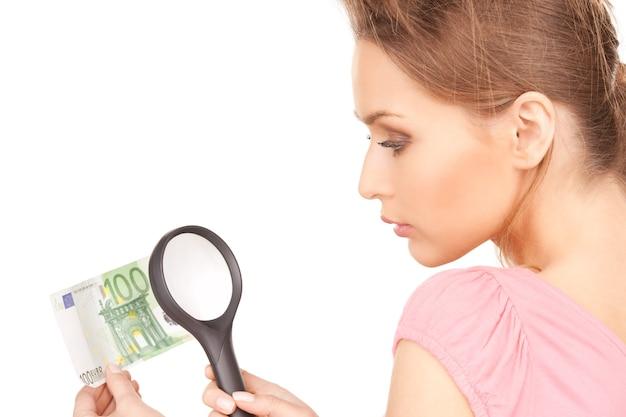 Mooie vrouw met vergrootglas en geld