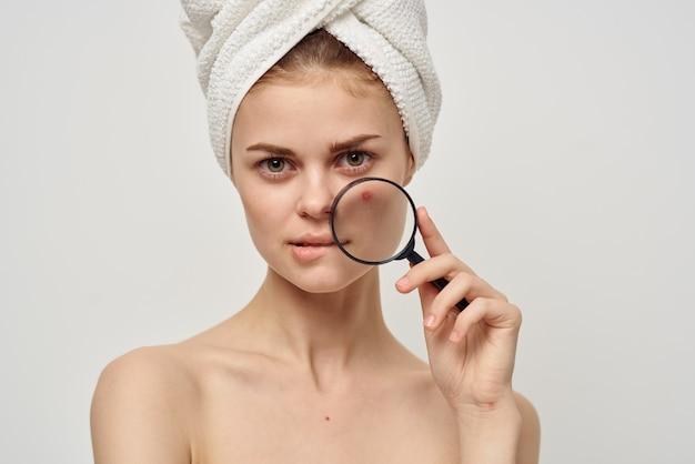 Mooie vrouw met vergrootglas in de buurt van gezicht acne acne huidverzorging uiterlijk