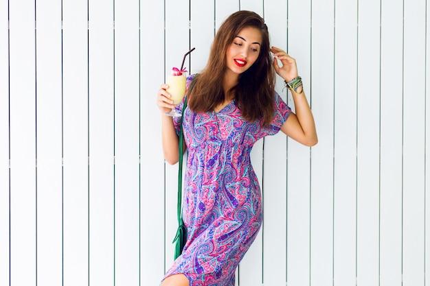 Mooie vrouw met verrassingsgezicht, die cocktail houdt en lange bohokleding draagt