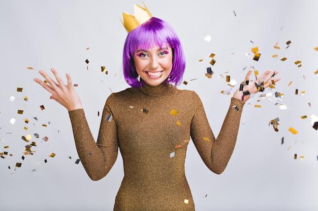 Mooie vrouw met violet kapsel met plezier in gouden klatergoud. ze draagt een gouden kroon, glimlachend