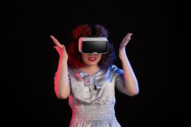 Mooie vrouw met virtual reality headset op donkere ondergrond