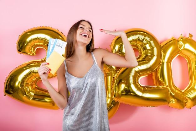 Mooie vrouw met vliegtickets en paspoort met 2020 nieuwe jaar ballonnen geïsoleerd over roze