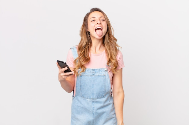 Mooie vrouw met vrolijke en rebelse houding, grappen makend en tong uitsteken en een smartphone vasthouden
