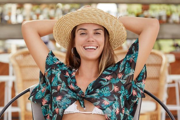 Mooie vrouw met vrolijke uitdrukking, gekleed in modieuze blouse en zomerhoed, houdt de handen achter het hoofd