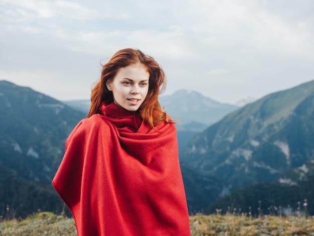 Mooie vrouw met warme deken in de bergen en rood haarmodel. hoge kwaliteit foto