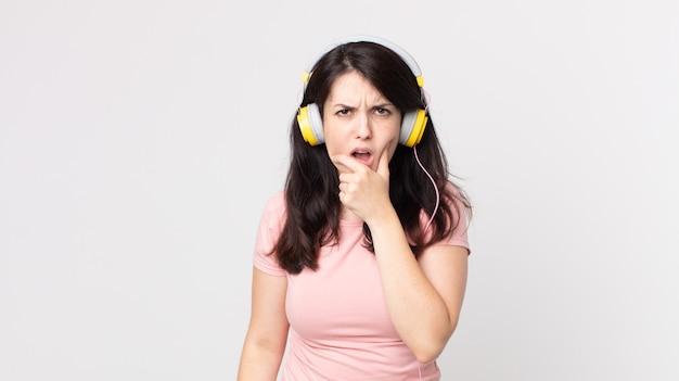 Mooie vrouw met wijd open mond en ogen en hand op de kin die muziek luistert met een koptelefoon