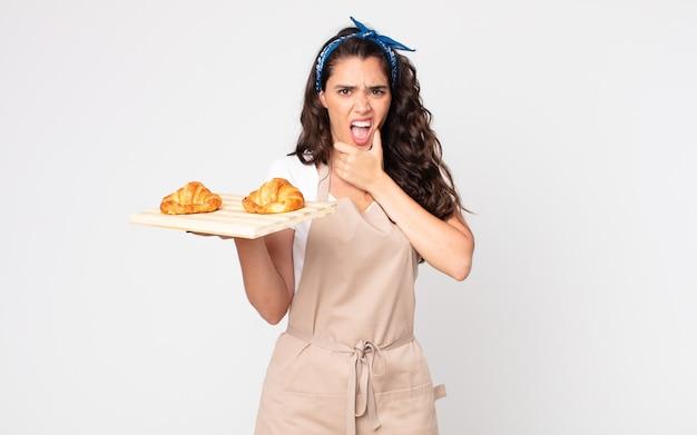 Mooie vrouw met wijd open mond en ogen en hand op kin en met een dienblad met croissants