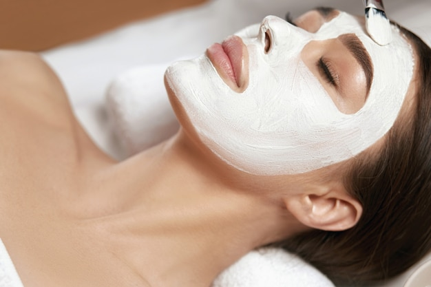 Mooie vrouw met wit klei gezichtsmasker bij beauty spa salon
