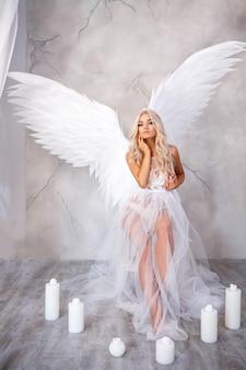 Mooie vrouw met witte vleugels op witte achtergrond