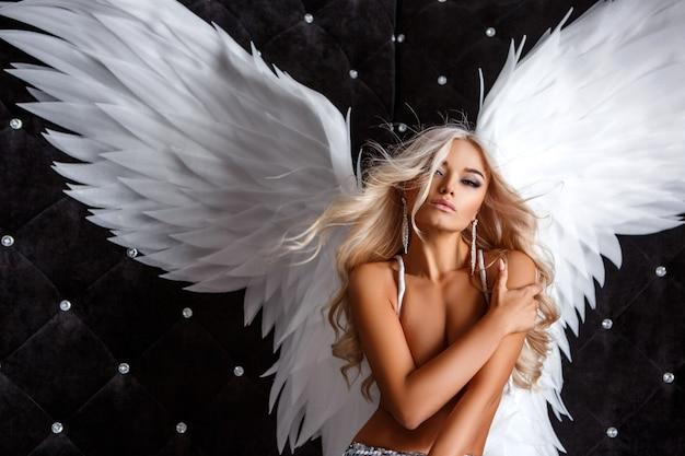 Mooie vrouw met witte vleugels op zwarte achtergrond