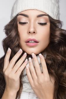 Mooie vrouw met zachte make-up, design manicure en glimlach in witte gebreide muts
