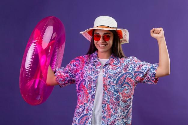 Mooie vrouw met zomerhoed en rode zonnebril met opblaasbare ring verlaten verheugend haar succes en overwinning haar vuisten balancerend glimlachend vrolijk klaar om concept vakantie staan