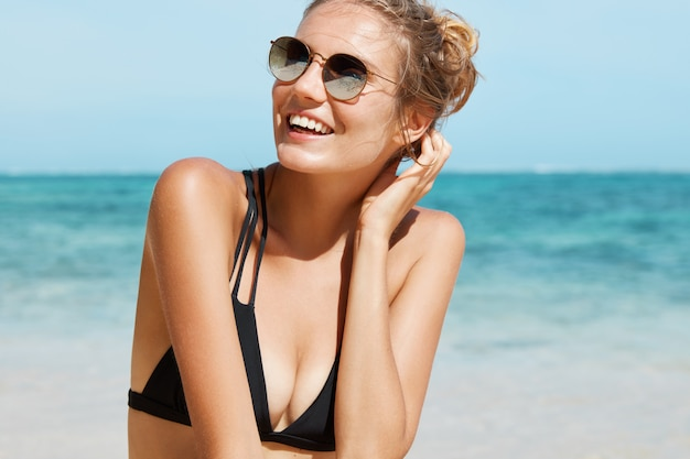 Mooie vrouw met zonnebril en zwempak op het strand
