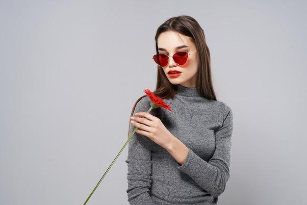 Mooie vrouw met zonnebril rode bloem rode lippen luxe